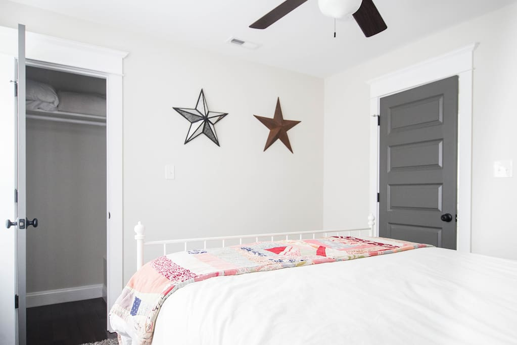 Guest bedroom with queen bed.  Alarm clock, essential oil diffuser, water bottles, ceiling fan, extra pillows blanket and hangers in the closet, memory foam mattress cover..We've thought of it all!