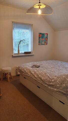 Tweede slaapkamer met een tweepersoonsbed (160cm) en opbergladen onder het bed. Kokosmat tapijt op de grond.