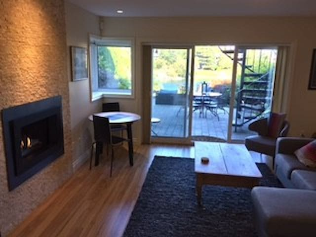 Living Room Looking out to water view and patio, gas fireplace, glass sliding doors with screens