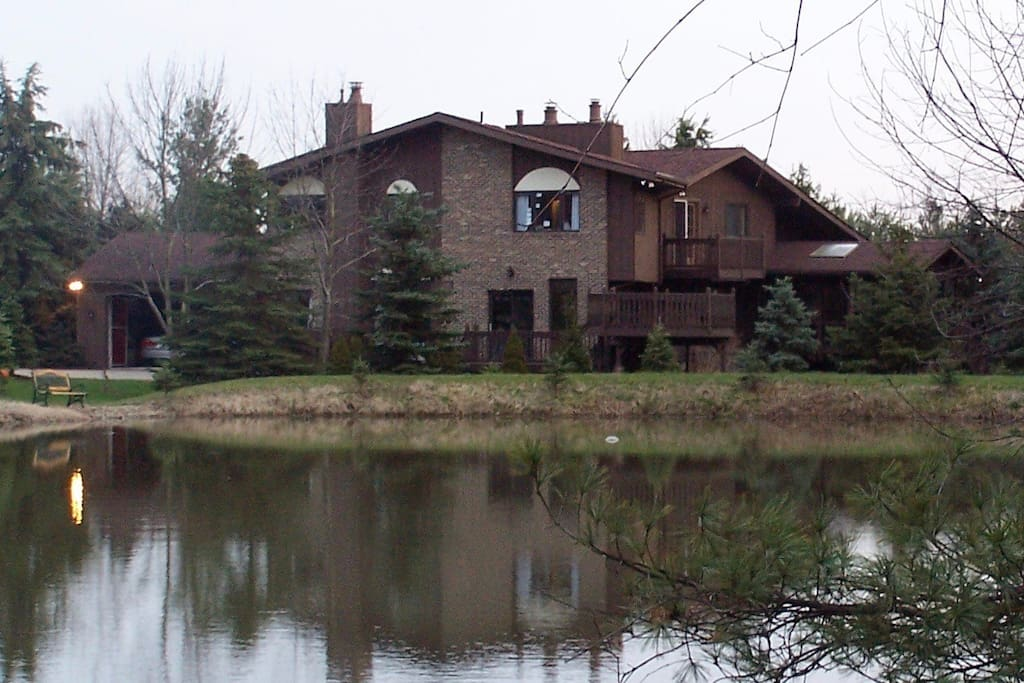 View of the back of the house from the bridge over the back lake.  There are walking trails through the woods and around the property (11 acres)