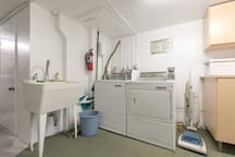 Showing basement laundry area with washtub and coin-op washing machine and dryer