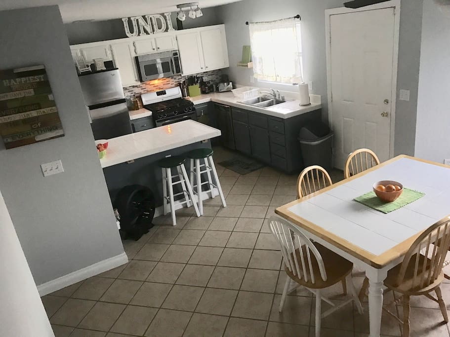 Kitchen and dining area with seating for six. The kitchen is fully stocked with pots and pans with a spacious food prep area.