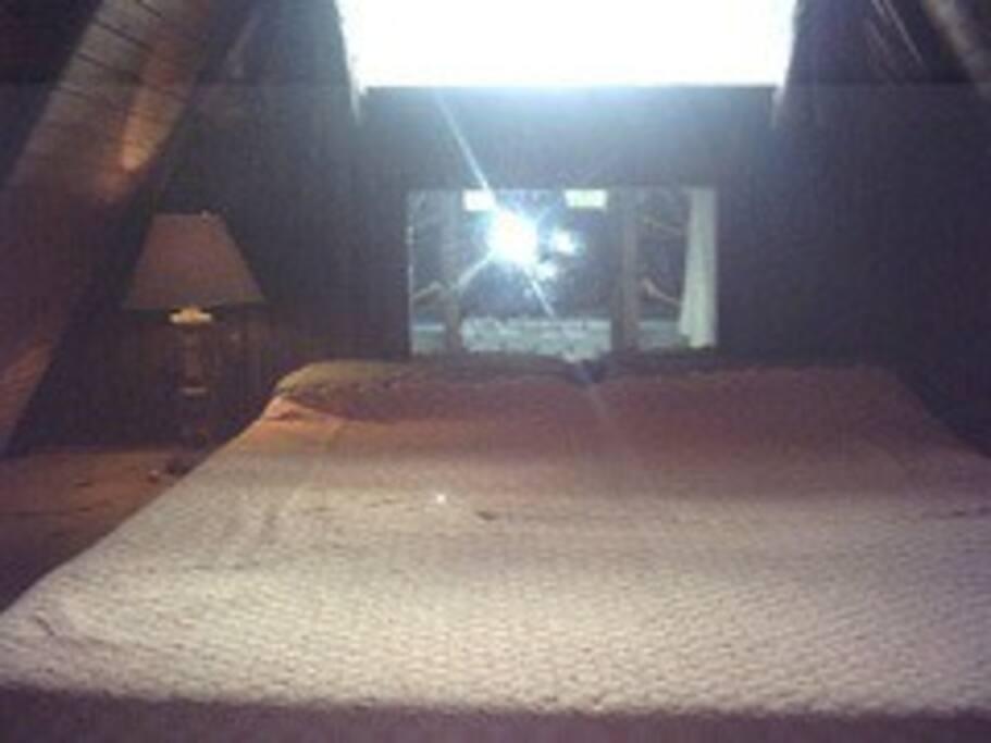 Dormitorio principal en entrepiso, el colchón va directamente en el piso de madera tal como en las originales cabañas alpinas.  Lo separa visualmente una cortina de hilo blanca.