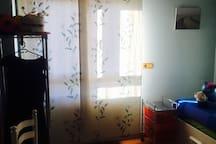 La habitación dispone de un ventanal, un perchero para la ropa, una silla y baño con lavabo y ducha.