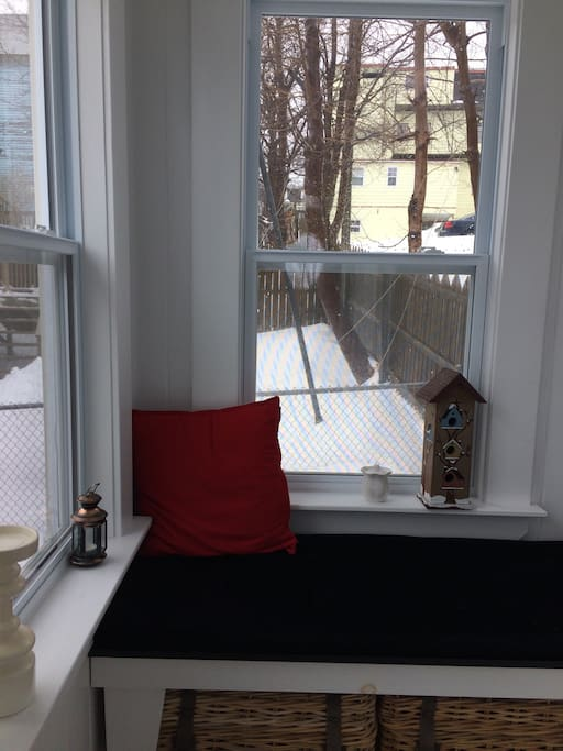 Comfortable window seat faces front lawn well off the street.