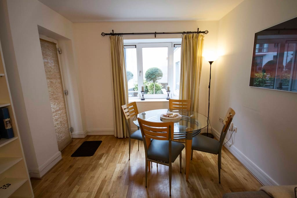 Entrance to apartment with dining table and chairs