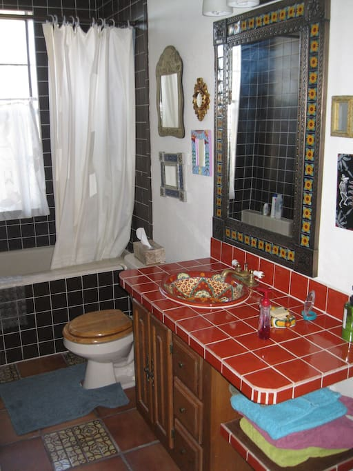 Shower, bathtub, toilet, sink in eclectic Mexican tile fashion.