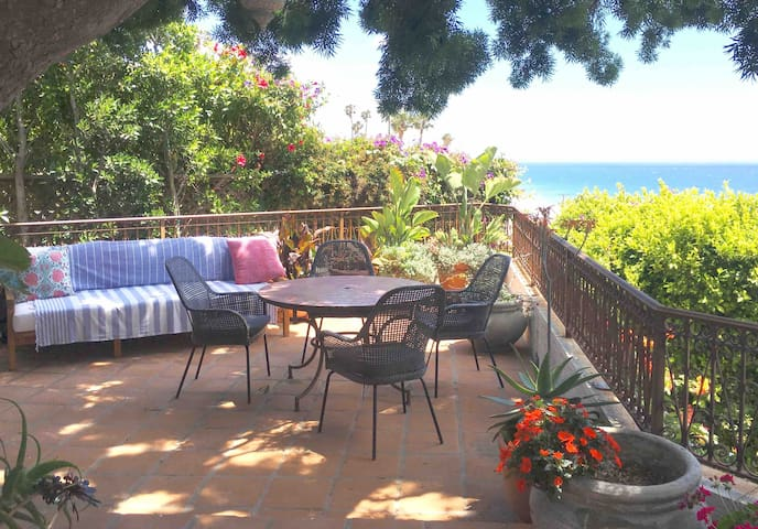 outdoor dining upper terrace. There is also a small table for coffee on the other side of the terrace, and a dining table on the lower deck