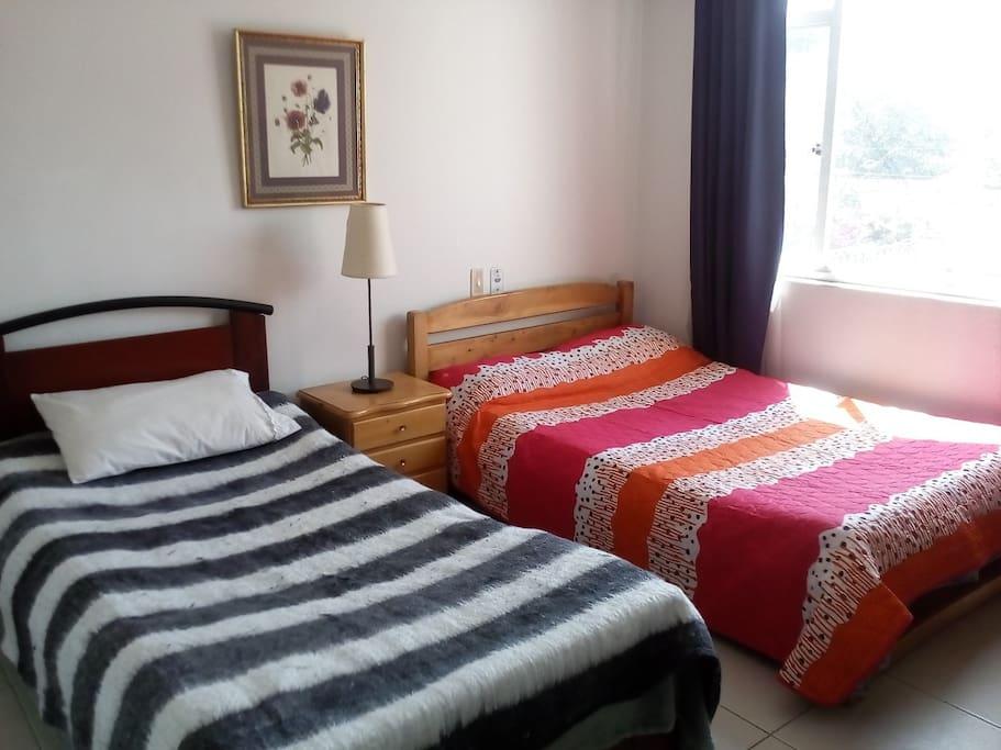 habitación con cama doble y una sencilla, muy acogedora