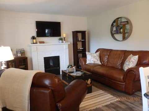 Comfortable living space with fireplace, leather couch and chair with ottoman.