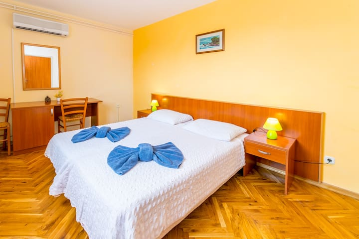 Comfortable bedroom, with two single beds connected together, offers TV and working table.