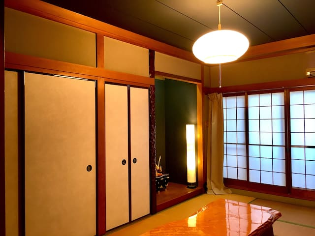 和式ルーム。 襖、ヒノキの床の間を設けた畳部屋。 就寝の2つ布団敷き。 4人用の座布団座卓。 エアコン付き。