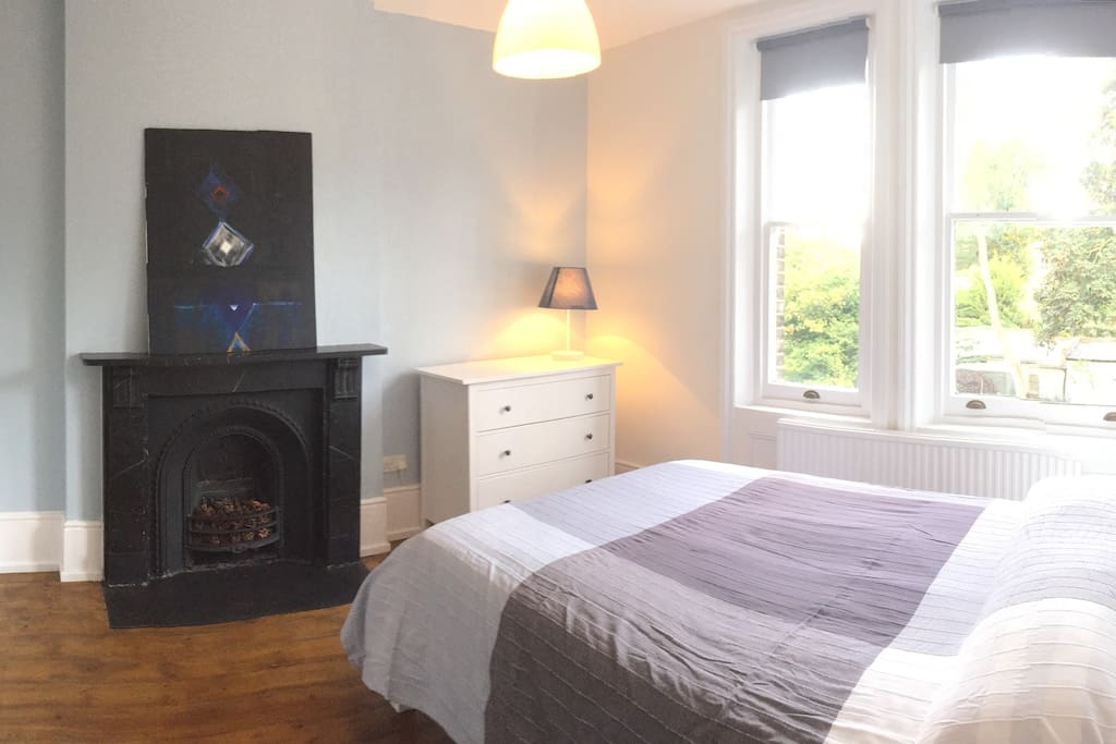 Large double bedroom overlooking the back garden with a beautiful authentic fireplace and convenient chest of drawers