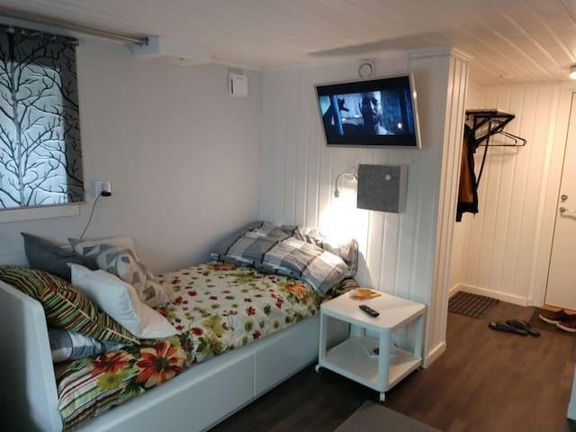 Säng, TV, BT-högtalare och hallen i bakgrunden. Sängen är utdrag bar till bredd 160 cm