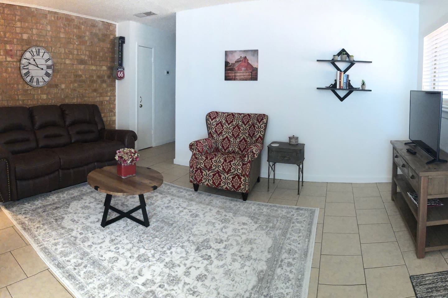 Living room with reclining leather sofa, comfortable chair and a color TV.