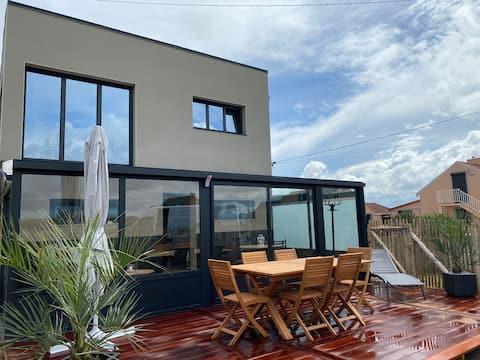 Maison cubique face à la mer avec accès direct.