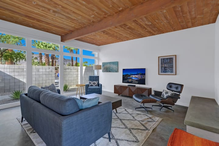 Open-concept living room lined with windows, finished cement floors, and warm wood ceilings.