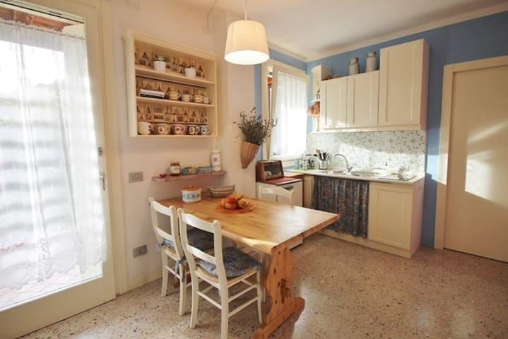 Cucina dotata di piastra elettrica, bollitore, macchina del caffè, microonde e utensili per cucinare.