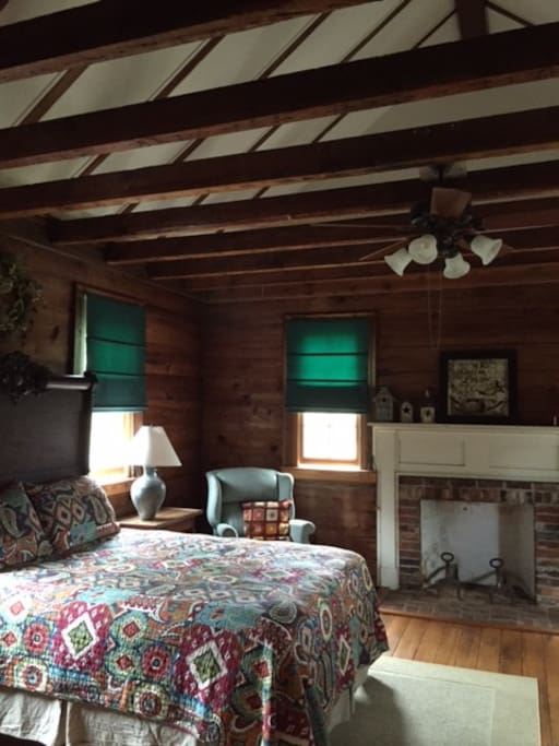 The Aviary Bedroom features soaring ceilings, original fireplace, and a comfy queen bed.