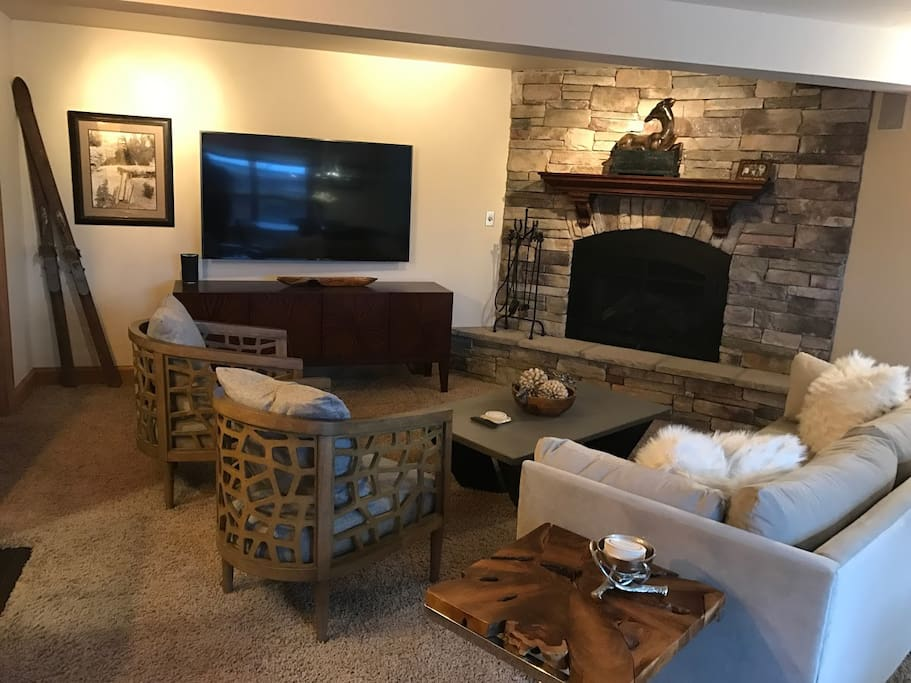 "Living Room with Stone Gas Fireplace and 65"" TV"