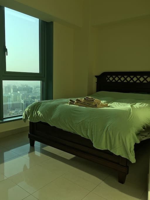 Queen size bed waiting for you with a sunrise view