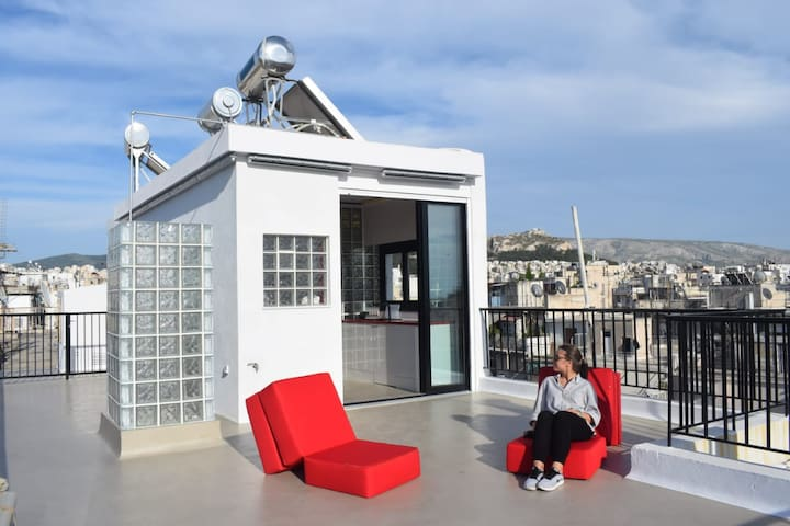 The property is located on the rooftop of the building, and consists of a small studio apartment, and a large private terrace with views of the whole of Athens.