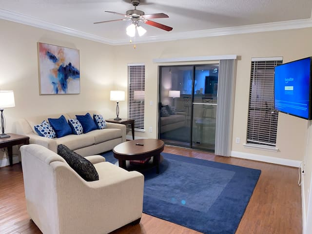 Large living room with sleeper sofa, upscale chair, and wood coffee table and end table. This living room also comes with high speed Wi-Fi, and a 55 inch 4k ultra HD smart TV.