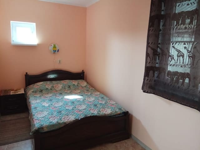 Комфортная двуспальная кровать в прохладной теневой комнате.