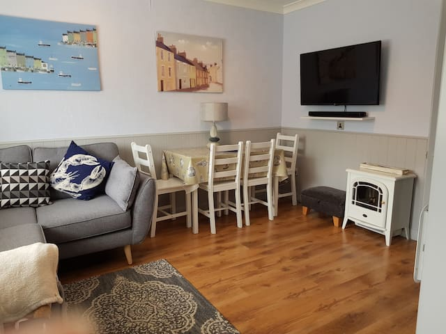"""Lounge/diner with a brand new corner sofa and 43"""" smart TV."""