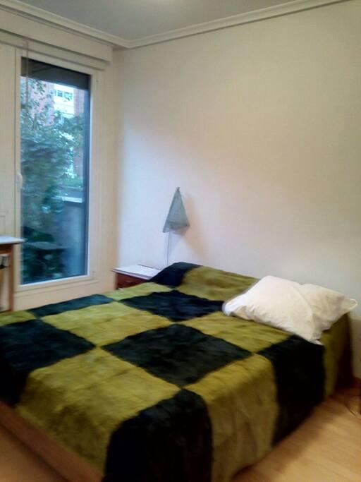 Dormitorio con cama doble y salida privada al jardin