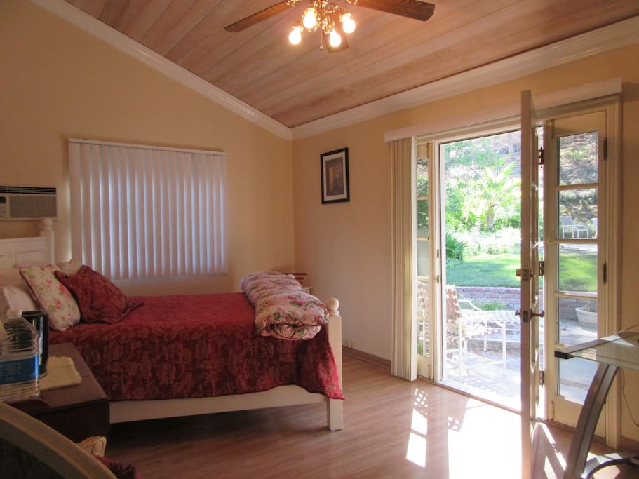 The guest unit. Queen sized bed, high wood beam ceiling, french door out to private yard and tennis court. Pool is on other side of the fence and easily accessible.