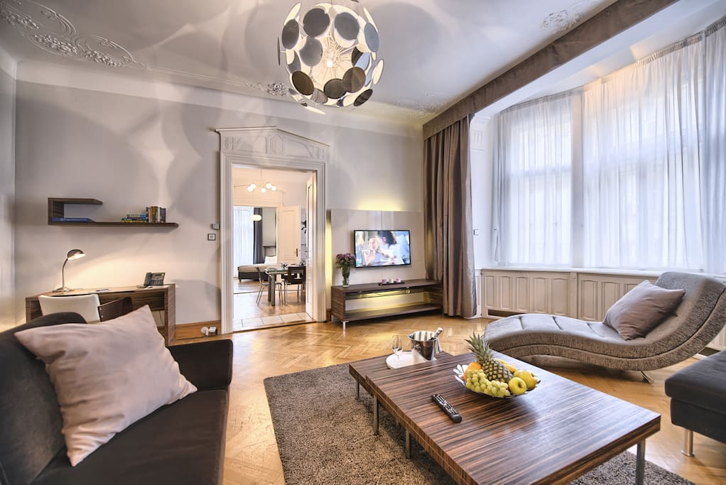 Spacious living room with comfortable sofas, flat-screen TV and a working desk