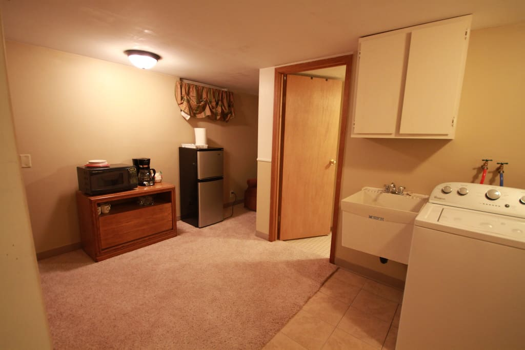 Mini kitchen area with microwave, coffee maker, refrigerator, and freezer.