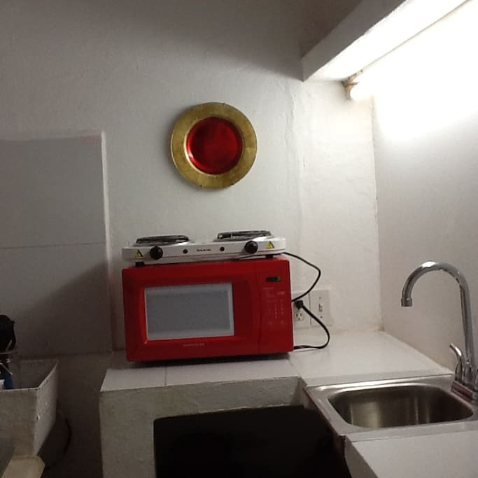 There is a small kitchenette, with microwave, small refrigerator, hot plate, sink, etc.