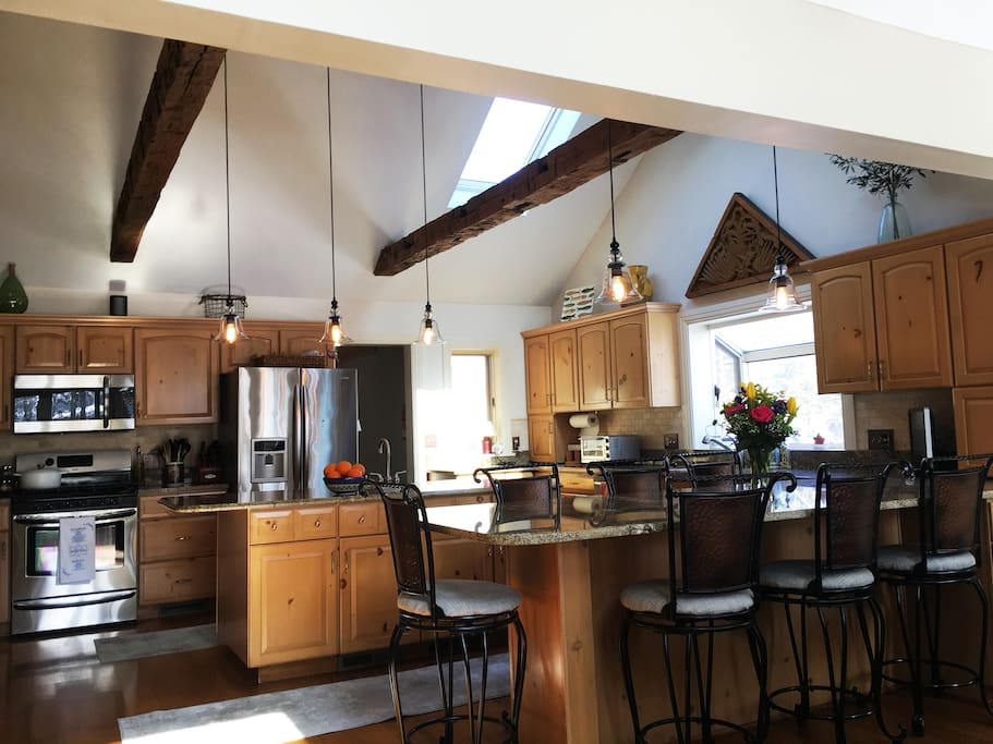 Gas stove and seating for six at the long counter. Barn wood beams on the high ceilings. Wine and beverage refrigerator attached to island.