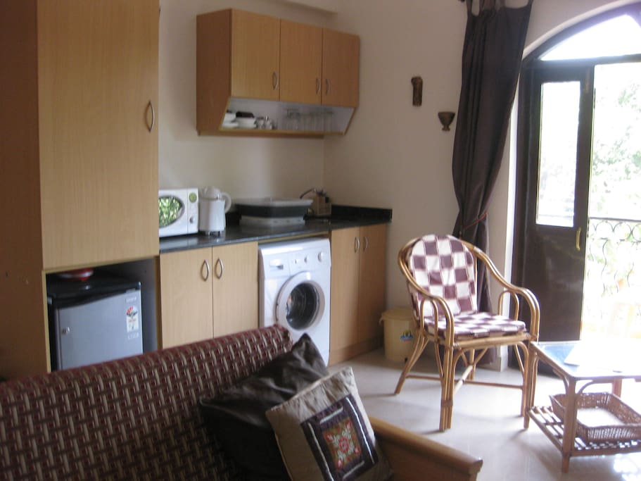 Kitchen area of the apartment with microwave, refrigerator,toaster,kettle, cooking hob, washing machine and full crockery, pans and glasses