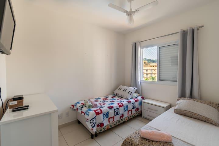 Quarto de solteiro com duas camas de solteiro, TV, ventilador de teto e cômoda.