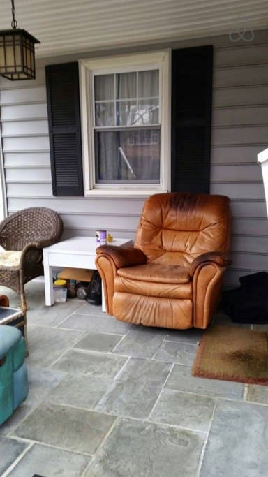 Big scruffy comfy recling leather chair out on front porch