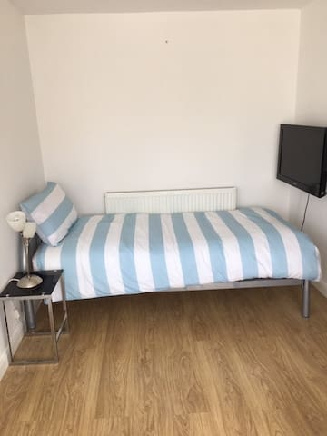 Bright sunny bedroom with 2 single beds, drawers and a TV