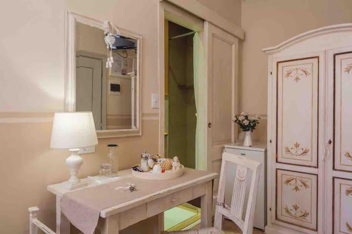 Camera singola con bagno .. Scrivania , armadio , frigorifero ed entrata del bagno
