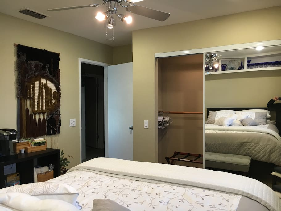 Mirrored closet doors with hangers in closet. Empty dresser drawers await your arrival!