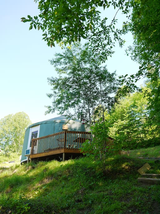 The yurt is situated alongside a private path that leads to a large grassy area, a creek, and the Solarius Eco Village.
