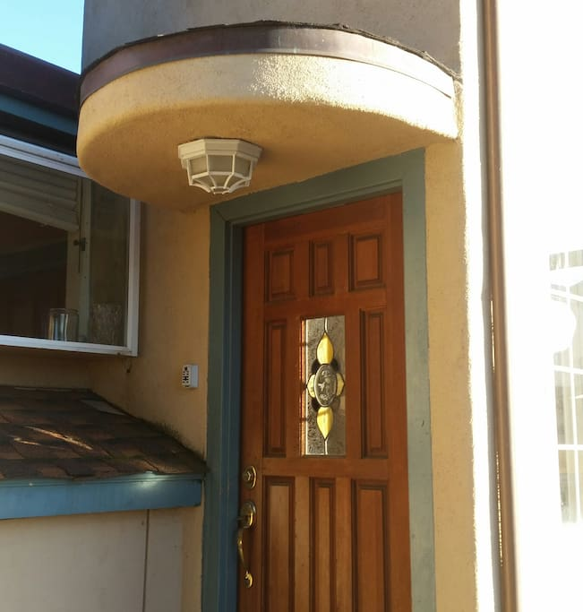 Entrance to cozy stucco and wood duplex.