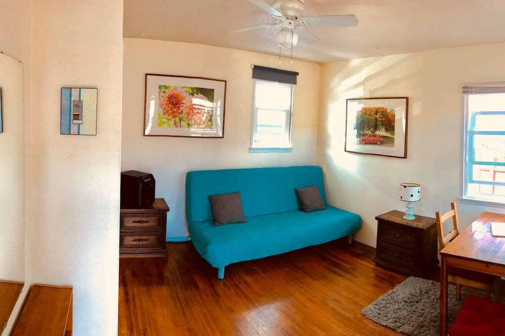 MAIN ROOM: Comfortable futon in sofa mode, window shade open. Hardwood floor, table for desk or dining.