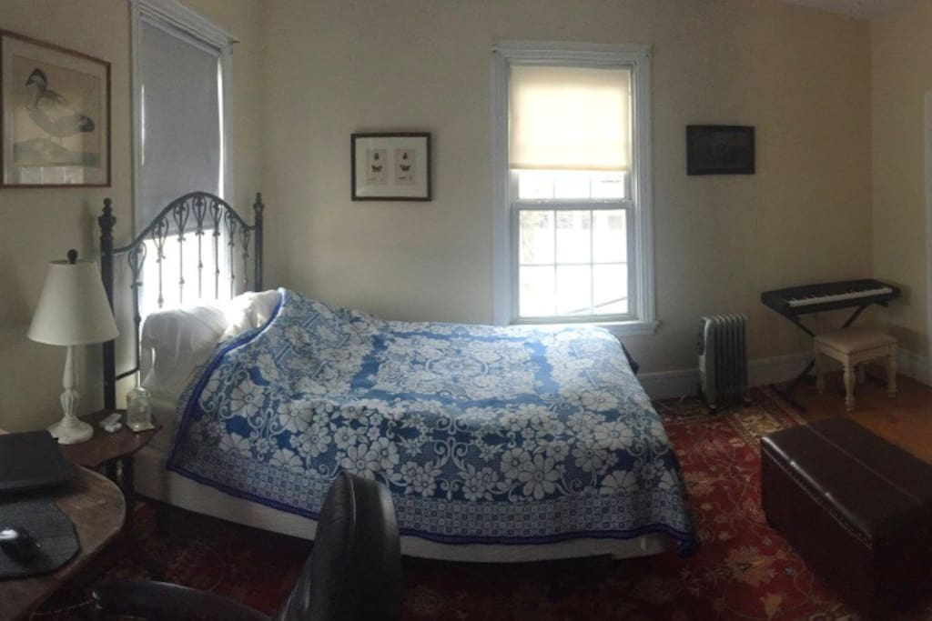 """Master bedroom has a workspace, walk in closet, 55"""" 4K TV, small keyboard piano and two dressers."""