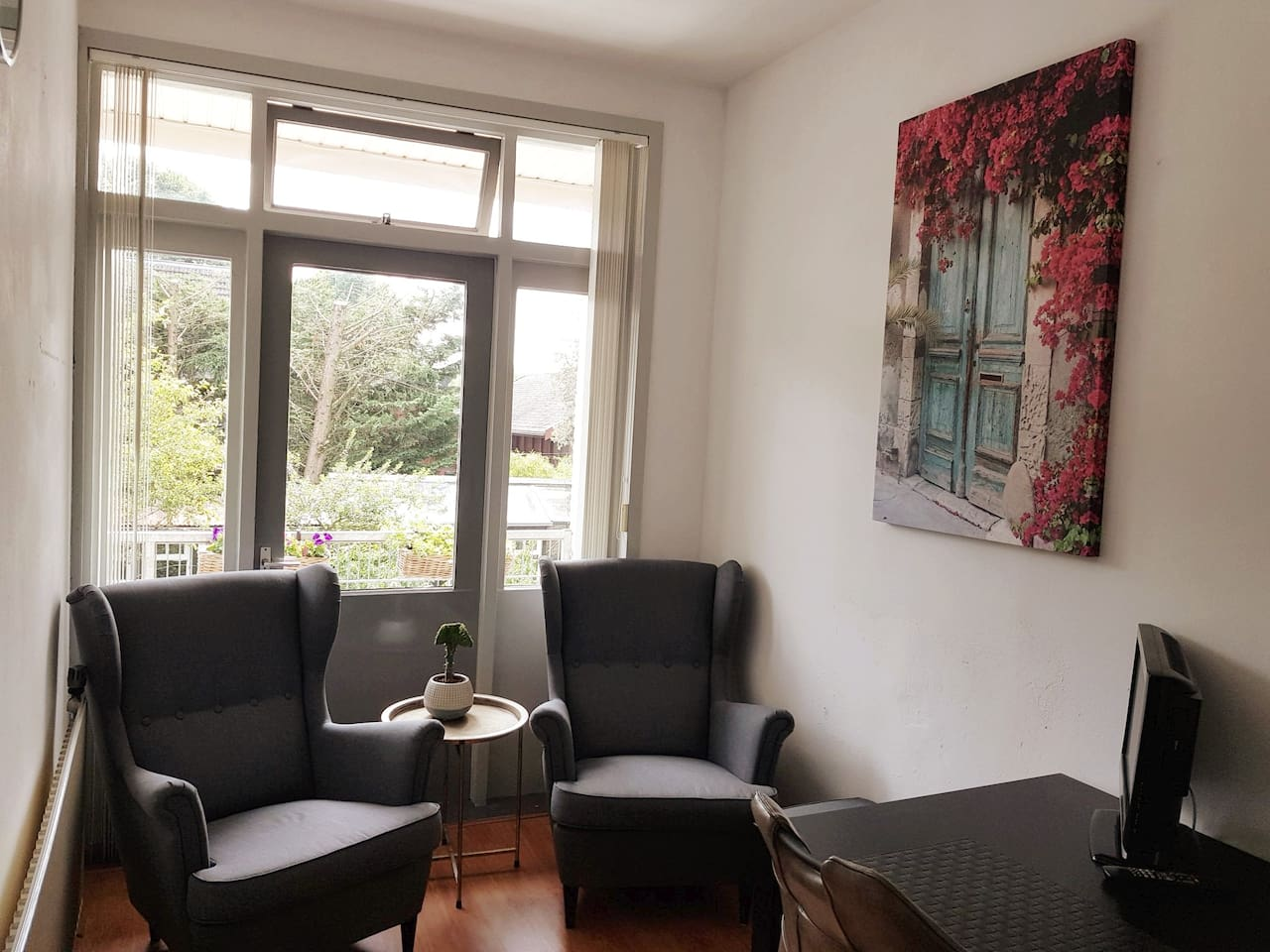 The livingroom of the apartment at the backside of the house. There is a sitting area and a large table . The apartment is suitable for 2 perons.  De huiskamer van het appartement aan de achterkant van de woning.  Het appartement is voor 2 personen.