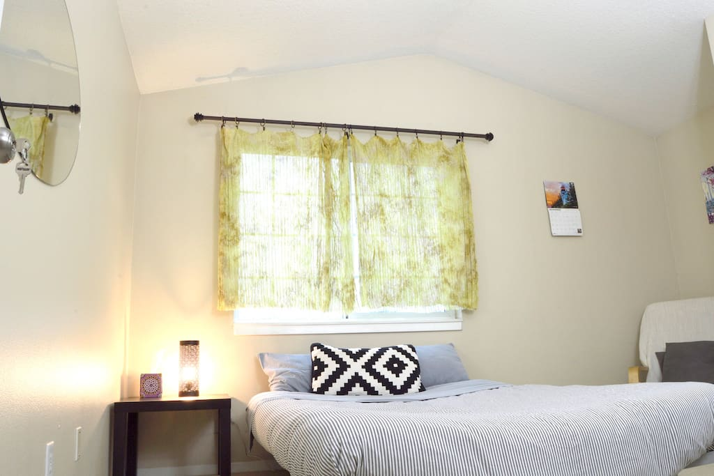 Bedside table with a bright modern lamp, and window facing towards the Willamette and West hills