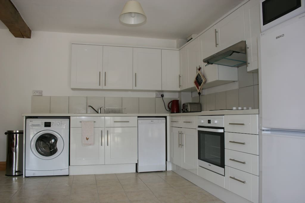 Fully equipped kitchen with oven, hob,  fridge, freezer, toaster, kettle, microwave washing machine, dishwasher and all the plates, cups and cook ware you need!