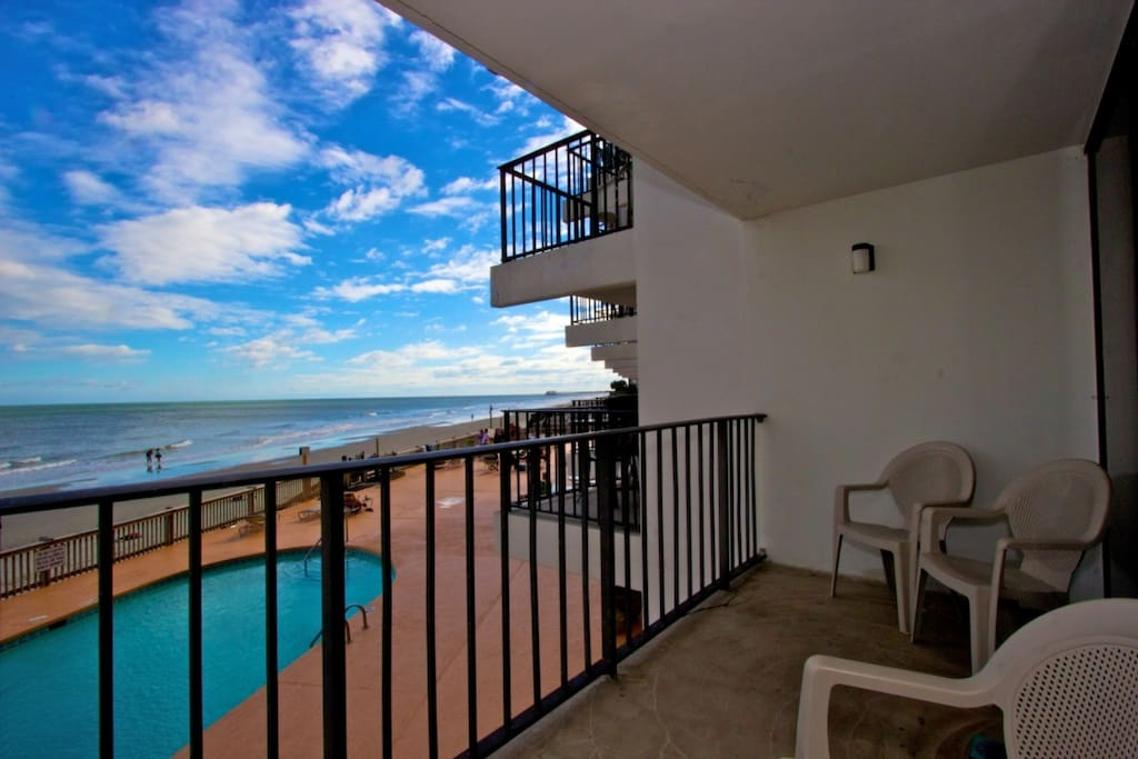 Enjoy the view of the pool, beach and ocean from your first floor balcony, one story above the ground.