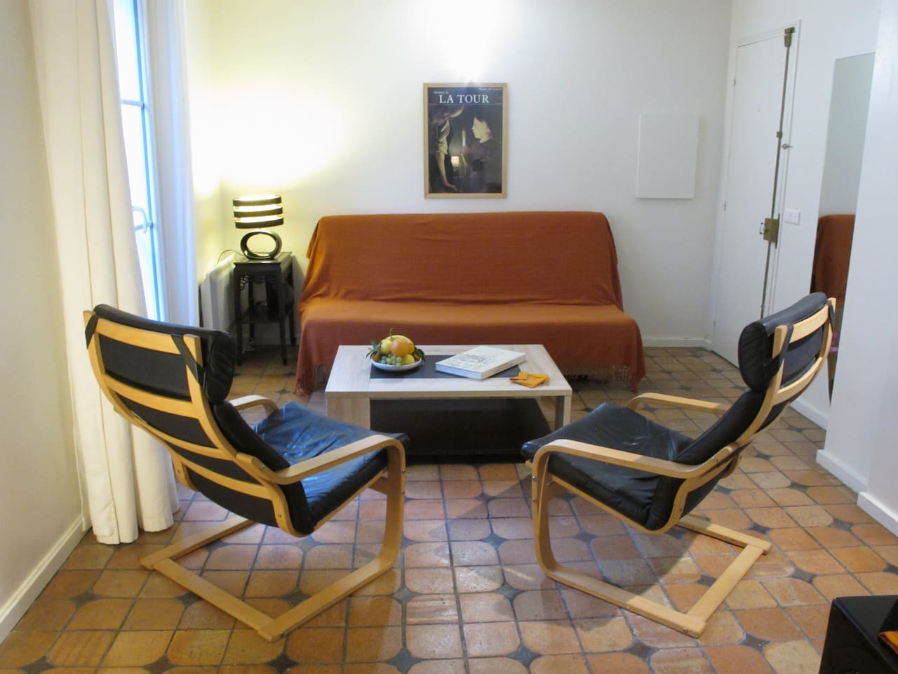 Living-room with a large window looking to the Pompidou museum. This sofa can be opened into a bed 140x200 CM